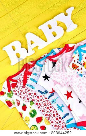 Babies organic clothes on sale. Infants beautiful set of organic rompers, yellow wooden background. Text baby and babies apparel.