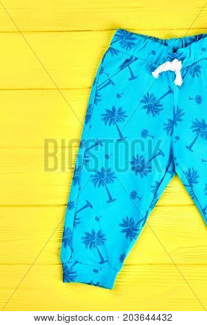 Kids beautiful blue harems. Infants brand cotton trousers on yellow wooden background. Toddlers brand apparel on sale.