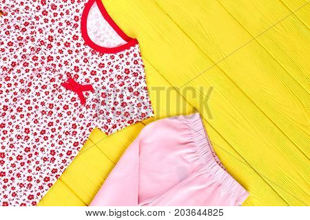 Baby-girl high quality clothes. Toddler girl adorable patterned dress and pink leggings, yellow wooden background. Kids new apparel on sale.