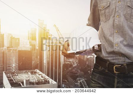 engineer holding helmet for workers security on background of new buildings and construction cranes on background of evening sunset cloudy sky Silhouette building constructions with crane lifts load