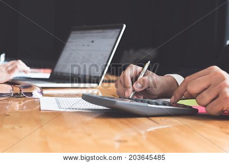 close up business man or lawyer accountant working on accounts using a calculator and writing on documents at his office