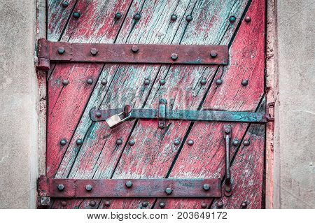 Vintage rustic wooden door secured with rusty metal latches and padlock closeup
