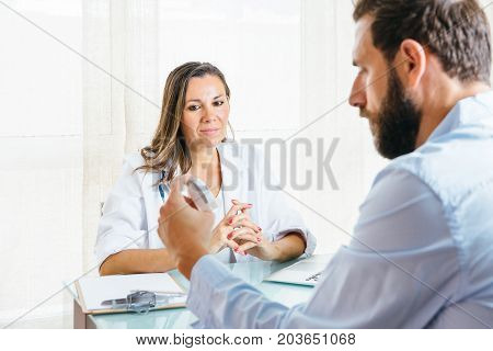 Female doctor is supervising a male patient while is using an aerosol inhaler at her office