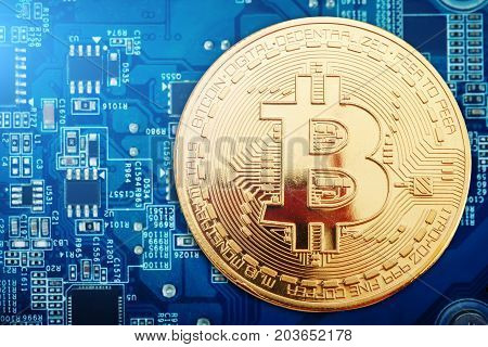 The gold coin of bitcoin lies on the video card. Business background.