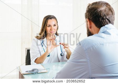 Female doctor is showing an aerosol inhaler to a man at her office