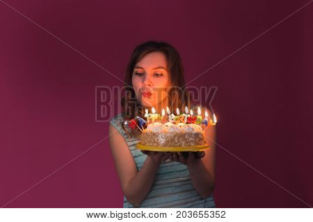beautiful caucasian girl blowing candles on her cake. Birthday, party and celebration concept.