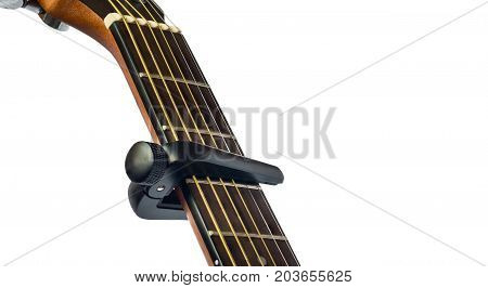 capo on guitar fingerboard white background close up