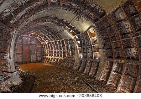 Abandoned old forgotten technical underground room. Bend of a rusty old tunnel