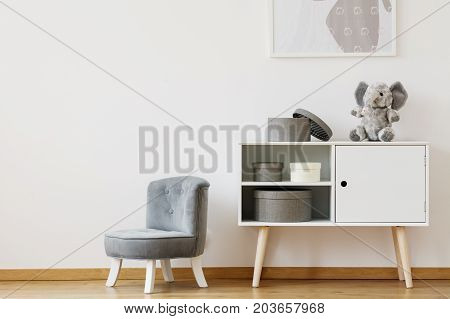 Grey Chair Next To White Shelf