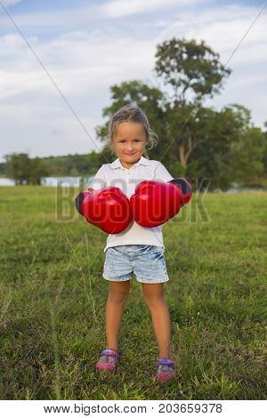 A young girl with wind blown hair wearing red boxing gloves.