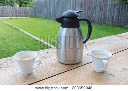 Thermos bottle with two mugs in a garden
