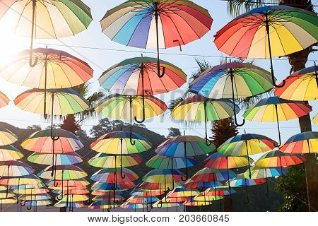 Colorful Umbrellas Background. Multi-colored Umbrellas In The Sky Floating Above The Street Against