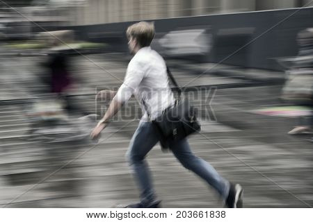 Young man in a hurry. Blurred ation on urban square after rain.