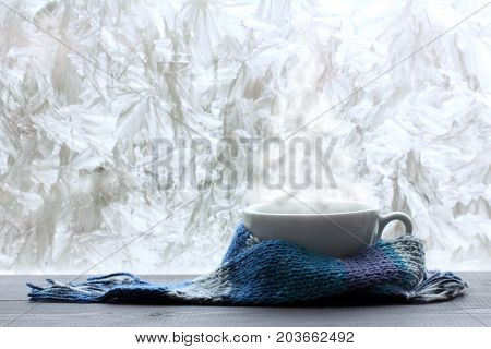 white mug in a blue scarf and warm steam in the form of a Christmas tree against the background of a frozen window/ warming Christmas fantasy