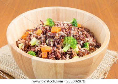 Vegetarian fried rice dish of red brown jasmine rice and riceberry with diced fresh broccoli and carrot in wooden bowl over natural sackcloth on wood table healthy dish concept (close-up view)
