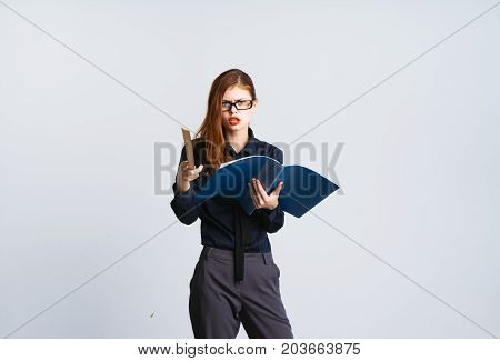 An angry woman is a teacher. Holds a magazine and a ruler
