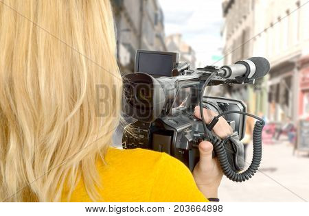young woman with his professional camcorder in the street
