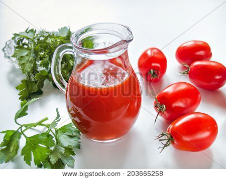 Fresh natural vegetable tomato juice is poured into a glass transparent jug near a tomato red and green greens on a white background
