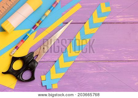 Kids paper bookmark on a wooden background with copy space for text. Simple paper crafts at home or school. Stationery on a desk. How to make a simple bookmark with paper. Top view