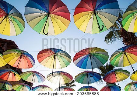 Colorful Umbrellas Background.multi-colored Umbrellas In The Sky Floating Above The Street Against P