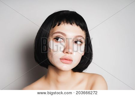The girl looks after her skin. She looks to the left. Woman with black hair