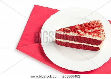 Red Velvet Cake sliced in piece on white plate over red placemat isolated on white background (Clipping path included) for celebrate X'mas season Valentines day or special holiday events with copy space for text insertion