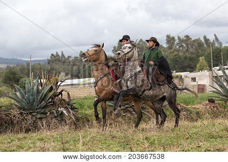 June 10 2017 Toacazo Ecuador: cowboys wearing traditional poncho riding their horses in the rain