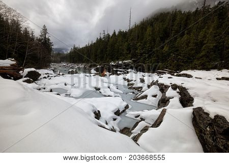 Nature view on the snow covered valley with the river. Picture taken near Tofino Vancouver Island British Columbia Canada.