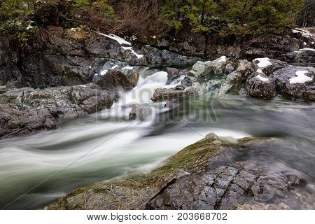 Nature view on the river flowing in between the rocks during winter. Picture taken near Tofino Vancouver Island British Columbia Canada.