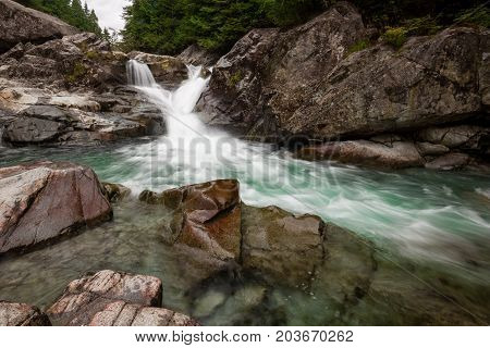 Nature landscape of a waterfall and river flowing in a canyon. Picture taken in Widgeon Falls Greater Vancouver British Columbia Canada.