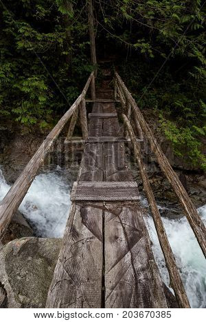 Wooden bridge over a flowing river on a hiking trail. Picture taken on a path to Widgeon Lake near Vancouver British Columbia Canada.