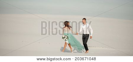 Bride in wedding dress and groom hold hands smile and walk barefoot in desert. Bride holds bouquet in her hand. Widescreen image. Copy space.