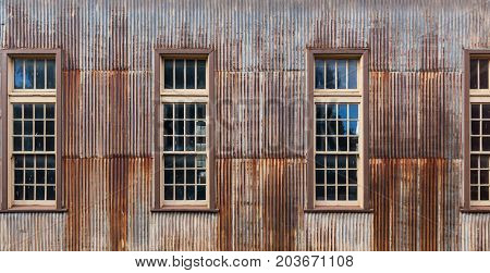Old rusty metal shed with tall windows closeup