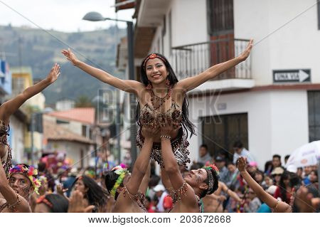 June 17 2017 Pujili Ecuador: female dancer held in the air by men performers at the Corpus Christi annual parade in the Andean town
