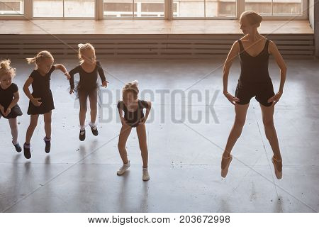 young beautiful blonde woman ballet dancer in black dress bulging pantyhose and pointe shoes teaches small fair-haired girls ballerinas in black dresses to jump and dance Russian ballet in a studio
