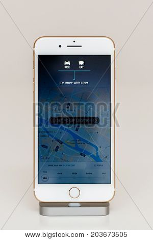 PARIS FRANCE - SEP 26 2016: New Apple iPhone 7 Plus in docking station after unboxing and testing by installing and running the app application software Uber Do more with uber Eat and Drive