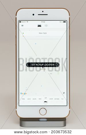 PARIS FRANCE - SEP 26 2016: New Apple iPhone 7 Plus in docking station after unboxing and testing by installing and running the app application software set pickup location New York in Uber App for Uber Lux