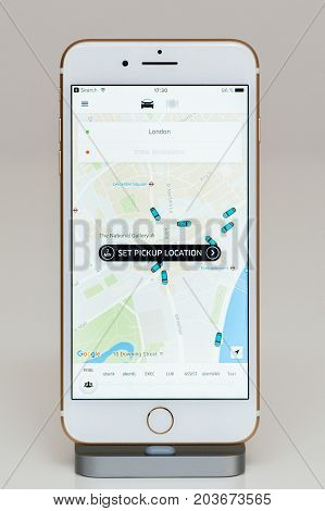 PARIS FRANCE - SEP 26 2016: New Apple iPhone 7 Plus in docking station after unboxing and testing by installing and running the app application software set pickup location in London for Uber driver transportation
