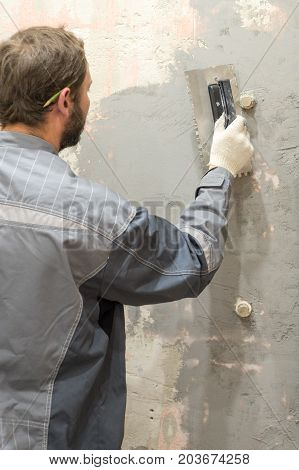 The worker makes plastering of the concrete wall.