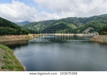 Pecingeanu dam lake on Dambovita river. accumulation lake hills and green forest background