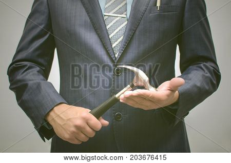 Business project development. Build your business. Open your own business. Under construction works. Business man in suit holding hummer in hands.