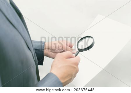 Business project review. Detective agent. Business man in suit looks through magnifying glass on the documents. Information search.