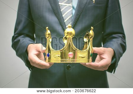 VIP client. Premium user concept. Success. Business man in suit holding in hands golden crown. Top manager. Best employee of the year award.