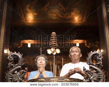 senior couple praying buddha with incense stick at temple