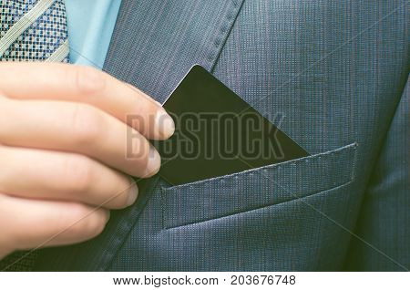 Business man pulls out his visiting card from suit pocket. Business meeting. Empty business card with copy space.