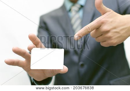 Business man is holding a business card by one hand and shows on her the index finger of the other hand. Visit card.