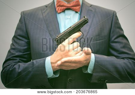 Elegant hitman in suit with red bow holds gun in front of himself. Smart Killer reloads the gun.