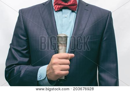 Showman. Man in suit with microphone in hands. TV reporter.