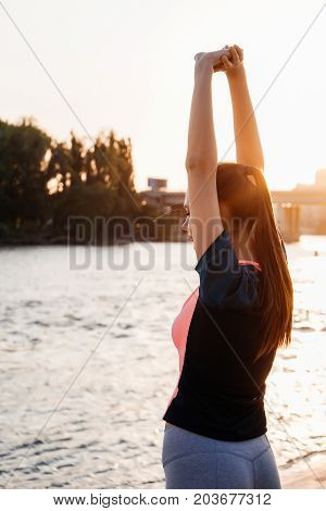 A sports woman sips on the riverbank, after a run, against a background of the city and the forest