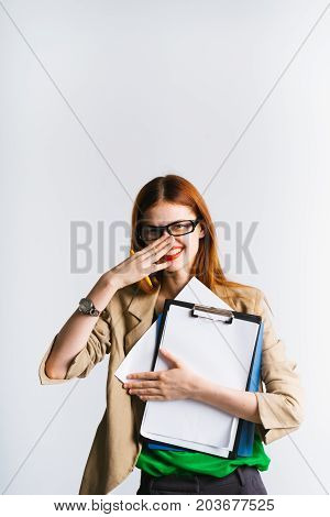 A beautiful business woman laughs, covered her mouth with her hand. The clock is on the arm. She holds a folder with documents in her hands
